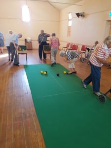 Monday Bowls club members bowling on the green indoors
